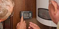 Une personne règle un thermostat